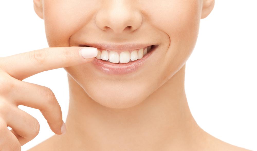 女性が健康的な歯を指し示す様子